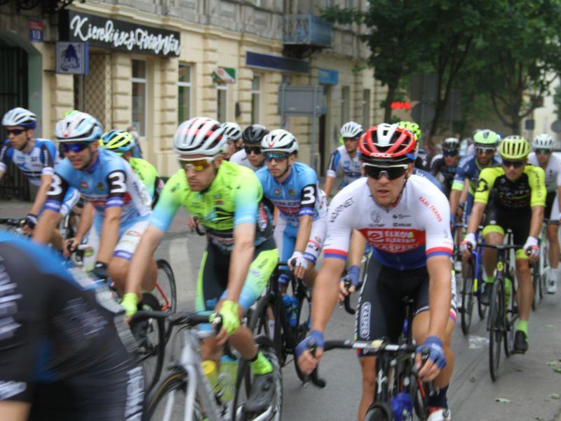 Na zdjęciu peleton wyścigu kolarskiego, który przemieszcza się ulicą Piłsudskiego. Kolarze w kolorowych koszulkach