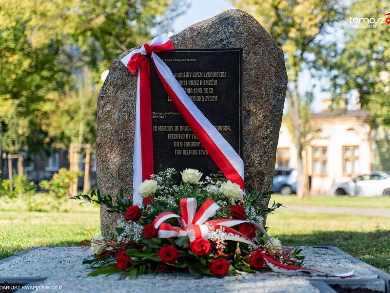 Zdjęcie obelisku z tablicą pamiątkową, przepasany biało-czerowną szarfą, przed leży wiązanka biało-czerwonych kwiatów