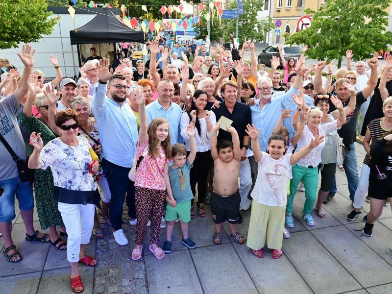 Na zdjęciu Karol Okrasa w otoczeniu grupy ludzi. Selfie zbiorowe podczas imprezy