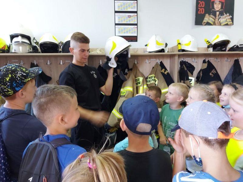 Na zdjęciu dzieci z pólkolonii na spotkaniu w Ochotniczej Straży Pożarnej. Strażak demonstruje im chełm strażacki