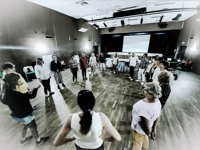 Na zdjęciu, w dużej sali ze sceną stoi grupka kobiet i mężczyzn w kółku