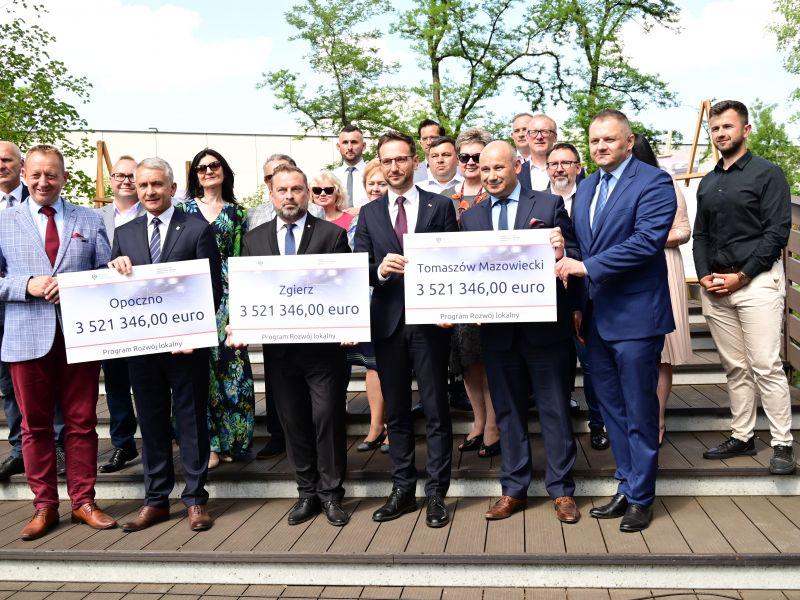 męzczyźni i kobiety stoją trzech trzyma tabliczki z kwotą dofinansowania