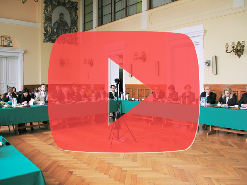 Na zdjęciu widać salę obrad, radni siędzą przy stole z zielonym suknem, widać dużą grafikę