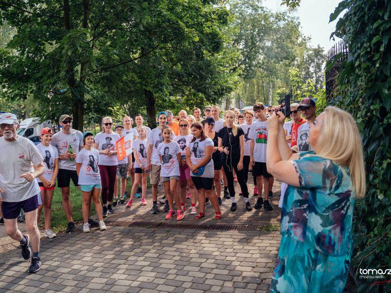 grupa ludzi w białych koszulkach na starcie biegu kobieta w niebieskiej sukience z uniesionym pistoletem startowym