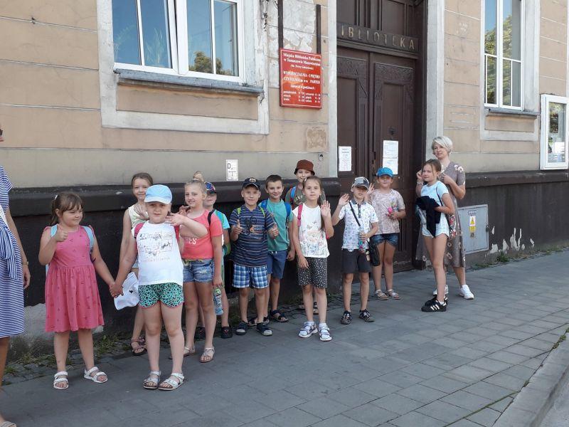 Na zdjęciu uczestnicy warsztatów bibliotecznych przed budynkiem MBP. Dzieci w strojach półkolonijnych i dwie wychowawczynie