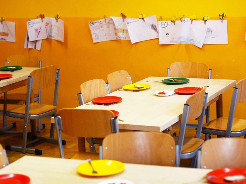 Na zdjęciu sala przedszkolna, stoliki po posiłku, na ścianach rysunki dzieci