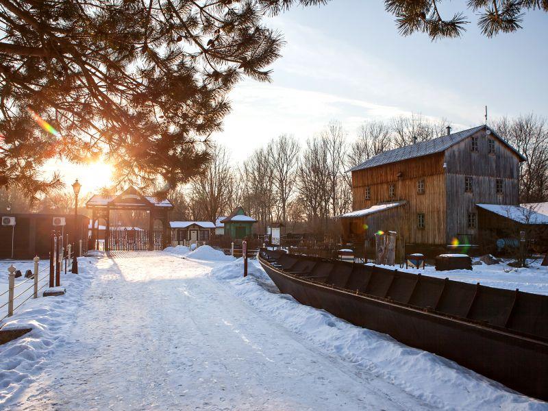 Na zdjęciu młyn-budynek Skansenu Rzeki Pilicy w aurze zimowej. Ośnieżone drzewa i dach oraz teren Skansenu