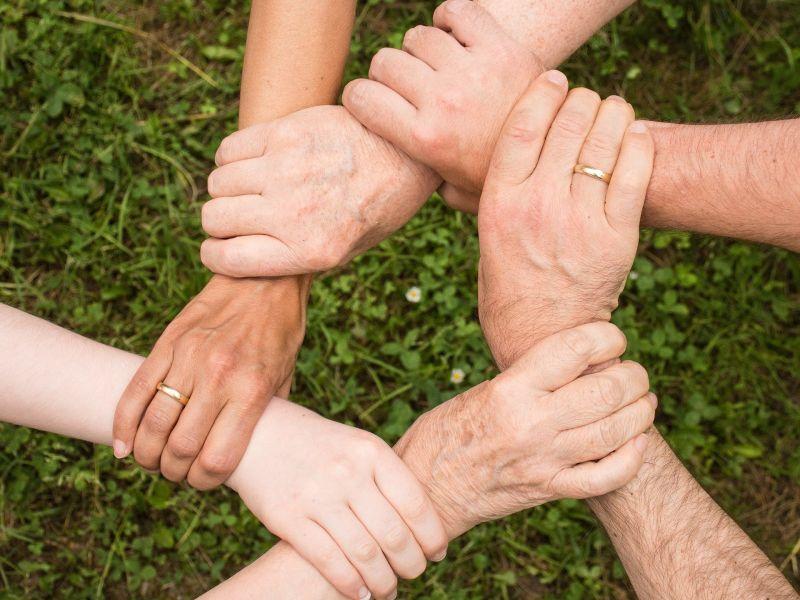 Na zdjęciu splecione w uścisku ręce na tle zielonego trawnika. Widać tylko przeguby rąk i dłonie we wzajemnym uścisku