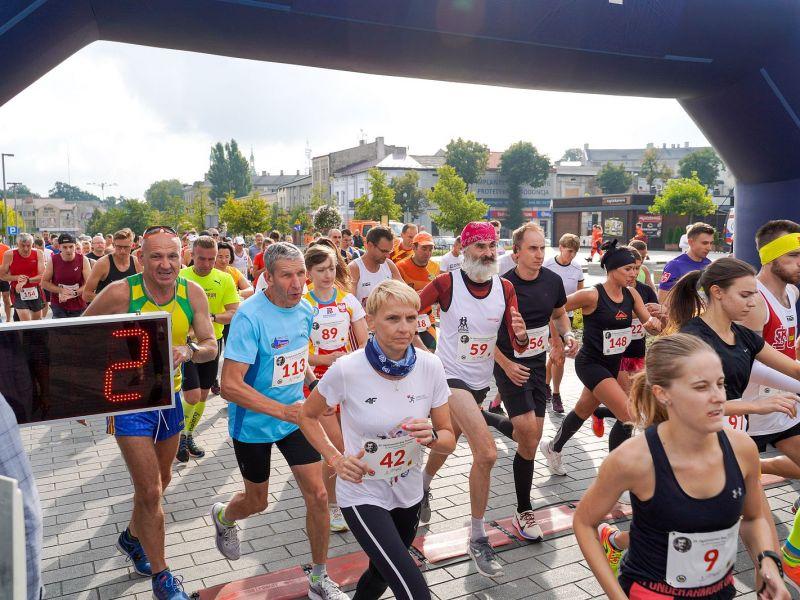 Na zdjęciu biegacze, uczestnicy Biegu im. B. Malinowskiego. Zdjęcie zrobione na starcie biegu, zawodnicy (kobiety i meżczyźni) w strojach sportowych z numerami startowymi na koszulkach