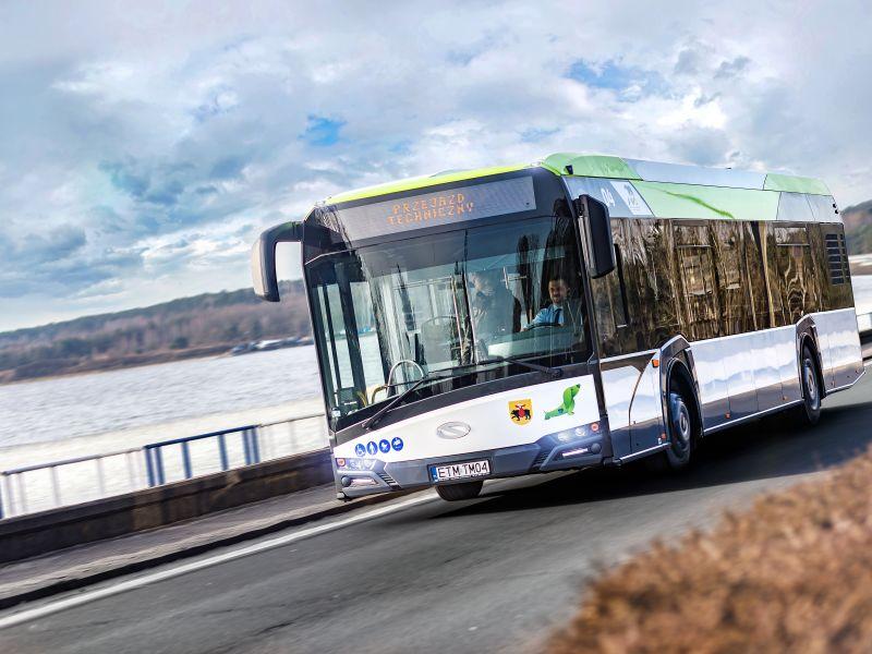 Na zdjęciu autobus pazażerski przejeżdżający przez tamę na Zalewie Sulejowskim, za szybą autobusu widoczny kierowca