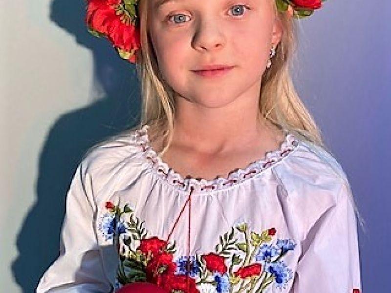 dziewczynka w wianku z kwiatów i czerwonym mikrofonem