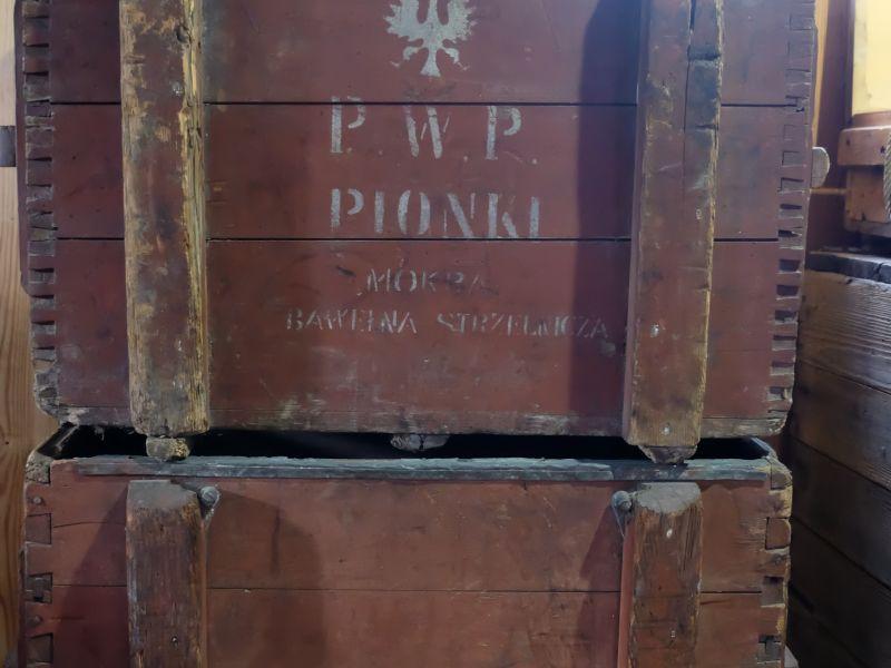 Na zdjeciu dwie drewniane skrzynie z II wojny światowej na ładunki wybuchowe, ustawione jedna na drugiej. Obecnie to eksponaty Skansenu Rzeki Pilicy