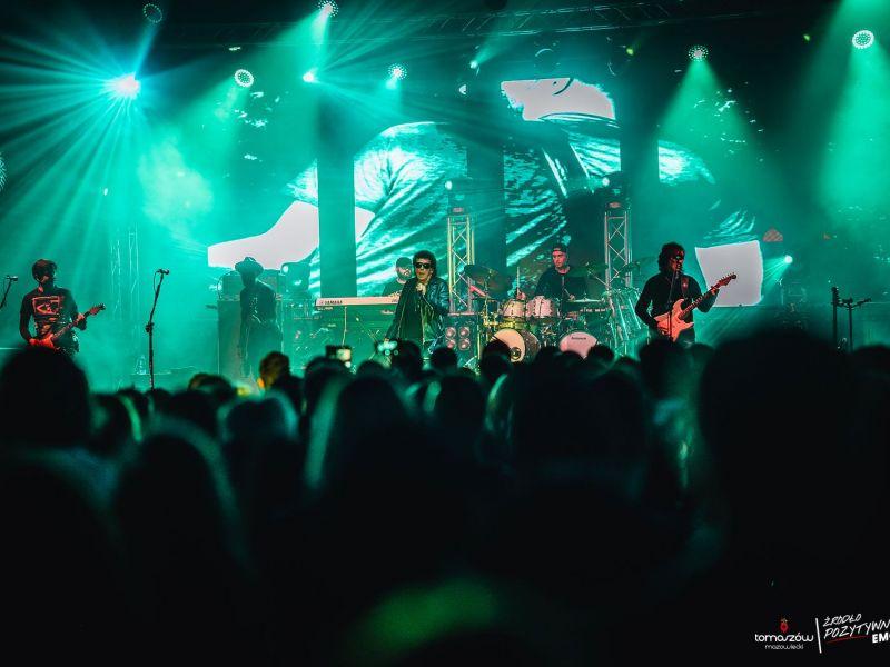 Na zdjęciu grupa Lady Pank podczas koncertu. Zielone światła sceniczne, publiczność przed sceną