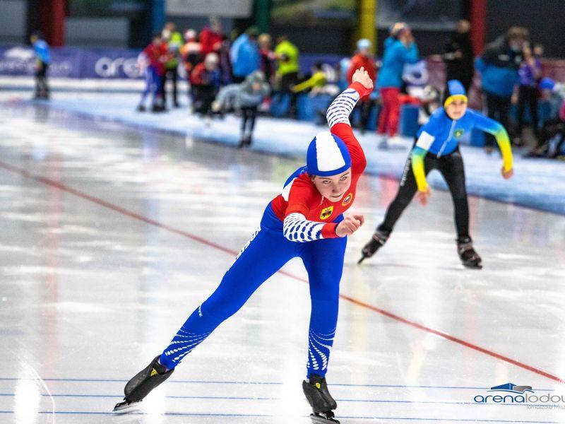 Na zdjęciu zawodnicy (dzieci) podczas startu w zawodach łyżwiarskich. Zawodnicy w kolorowych kombinezonach, na łyżwach na torze lodowym