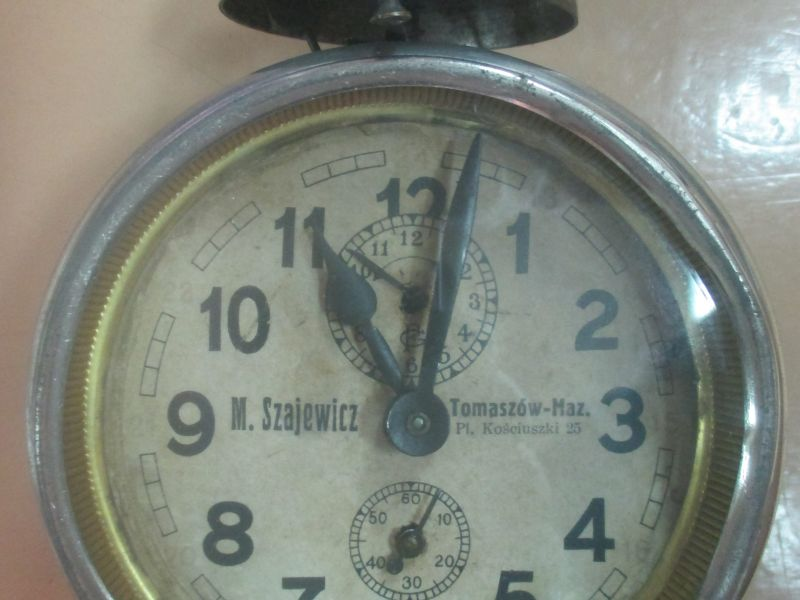Na zdjęciu budzik z okresu międzywojennego należący do fabryki M. Szajewicza. Przód budika, tarcza, wskazówki, sekundnik. Budzik stoi na nóżkach
