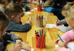 Na zdjęciu grupa przedszkolaków podczas zajęć plastycznych wykonujących rysunki
